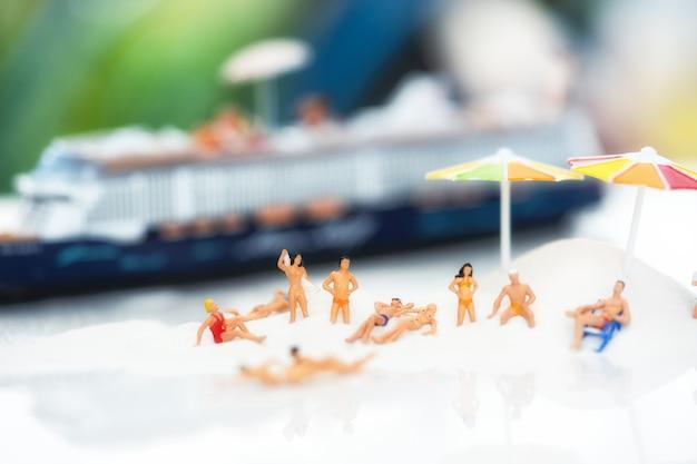 Miniaturleute, reisende, die auf dem sandkasten verziert werden, der im sommerthema verziert Premium Fotos