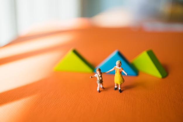 Miniaturleute, schwester und junger bruder, die auf tangrampuzzlespielhintergrund unter verwendung als bildungs- und familienkonzept gehen Premium Fotos