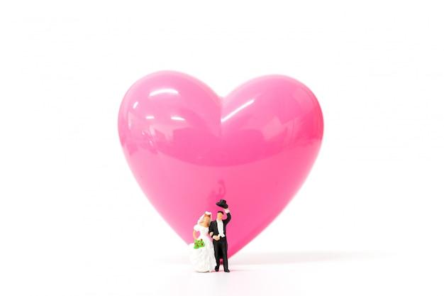 Miniaturleute verbinden mit rosa herzen auf weißem hintergrund Premium Fotos