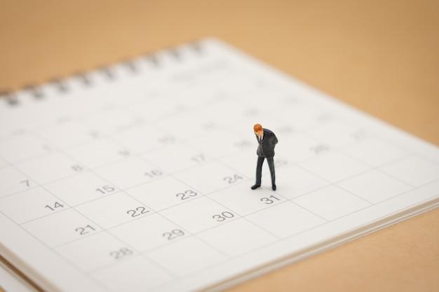 Miniaturleutegeschäftsmänner, die auf weißem kalender stehen Premium Fotos