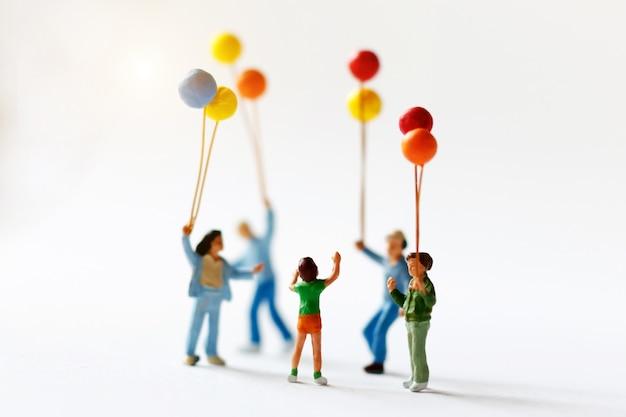 Miniaturleutekinder, die ballon mit sonnenlicht, glückliches familientageskonzept halten. Premium Fotos