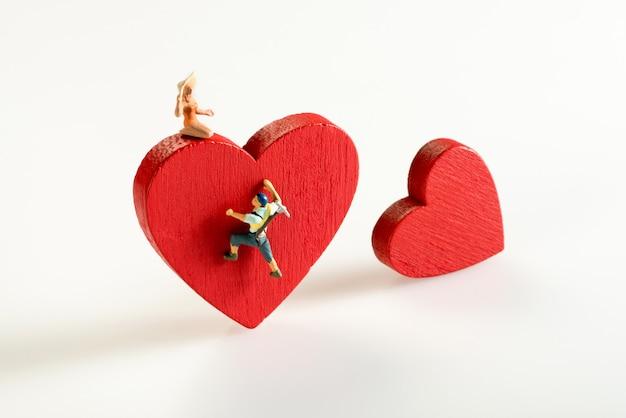 Miniaturmann, der ein rotes herz klettert Premium Fotos