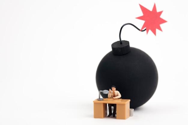 Miniaturmann, der mit der bombe bereit arbeitet zu explodieren Premium Fotos