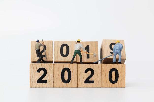 Miniaturmenschen: arbeiterteam schafft holzblock nummer 2020 Premium Fotos