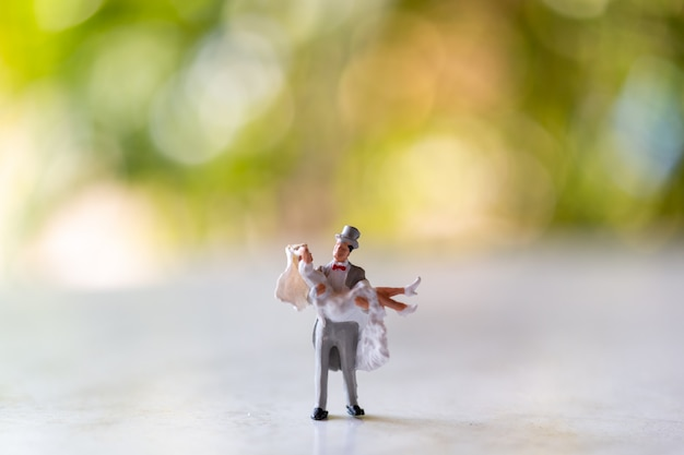 Miniaturmenschen: braut und bräutigam im freien mit grünem bokeh-hintergrund und kopierraum für text Premium Fotos