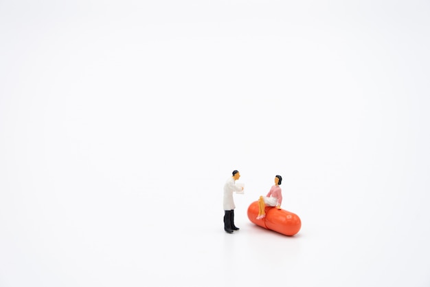 Miniaturmenschen konsultieren sie einen arzt, um nach gesundheitlichen problemen zu fragen. jährlicher gesundheitscheck oder arzt konsultieren. Premium Fotos
