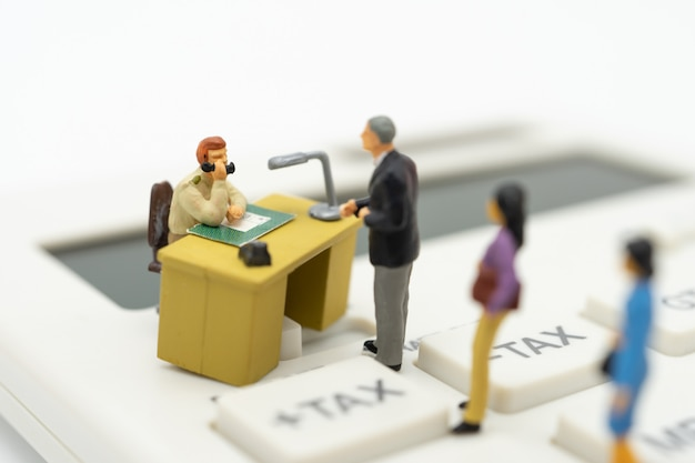 Miniaturmenschen lohnliste jährliches einkommen (tax) für das jahr auf dem taschenrechner. Premium Fotos