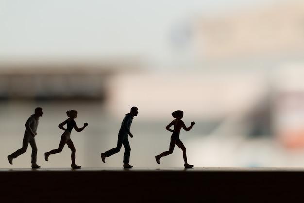 Miniaturmenschen: silhouette eines läufers Premium Fotos