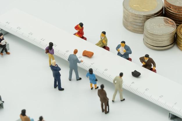 Miniaturmenschen verwenden eine bareinzahlung. am bankschalter oder beim finanzinstitut. Premium Fotos