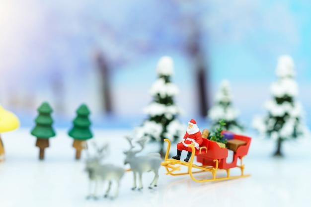 Miniaturmenschen: weihnachtsmann sitzend rentierschlitten mit gruß oder postkarte und weihnachtsbaum. Premium Fotos