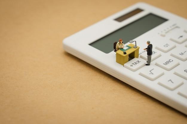 Miniaturmenschen zahlschlange jährliches einkommen (tax) für das jahr auf dem rechner. Premium Fotos