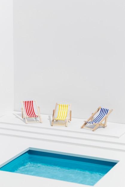 Miniaturzusammensetzung von sonnenliegen neben dem schwimmbad Kostenlose Fotos
