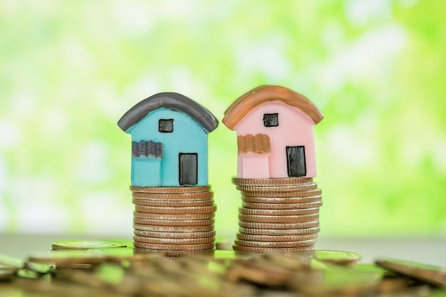 Minihaus auf stapel münzen mit grüner unschärfe. Kostenlose Fotos