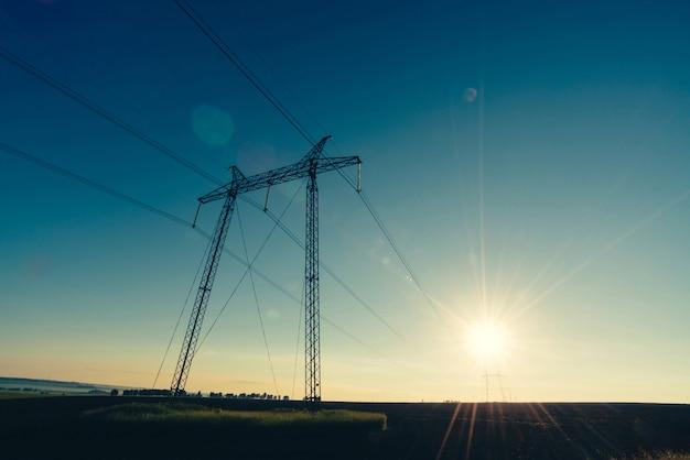 Minimale naturlandschaft mit silhouetten von stromleitungen im feld gegen sonnigen himmel Premium Fotos