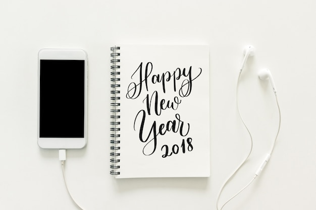 """Minimaler Arbeitsplatz - kreatives flaches Lagefoto des Arbeitsplatzschreibtisches mit """"2018 guten Rutsch ins Neue Jahr"""" auf Sketchbook und Handy mit leerem Bildschirm und Kopfhörer auf weißem Hintergrund. Draufsicht, Konzept des neuen Jahres. Kostenlose Fotos"""