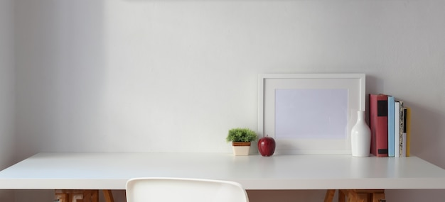 Minimaler arbeitsplatz mit kopienraum und leerem rahmen mit büchern auf weißer tabelle und weißer wand Premium Fotos