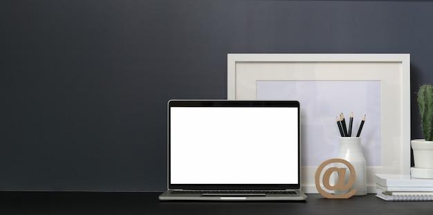 Minimaler arbeitsplatz mit offener laptop-computer des leeren bildschirms und modell herauf rahmen Premium Fotos