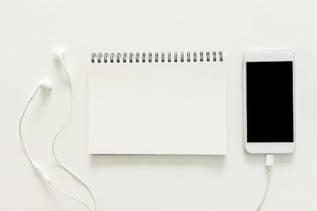 Minimaler Arbeitsraum - Kreativ flach legen Foto von Arbeitsbereich Schreibtisch mit Skizzenbuch und Handy mit leeren Bildschirm auf Kopie Raum weißen Hintergrund. Draufsicht, flache Laienfotografie. Kostenlose Fotos