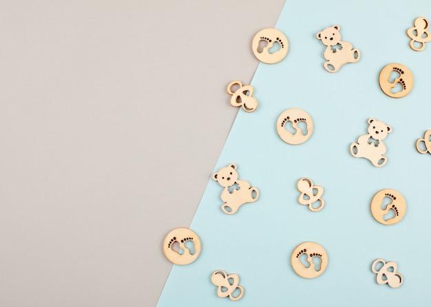 Minimaler dekorativer pastellhintergrund mit kleinen holzfiguren für neugeborenen geburtstag Premium Fotos