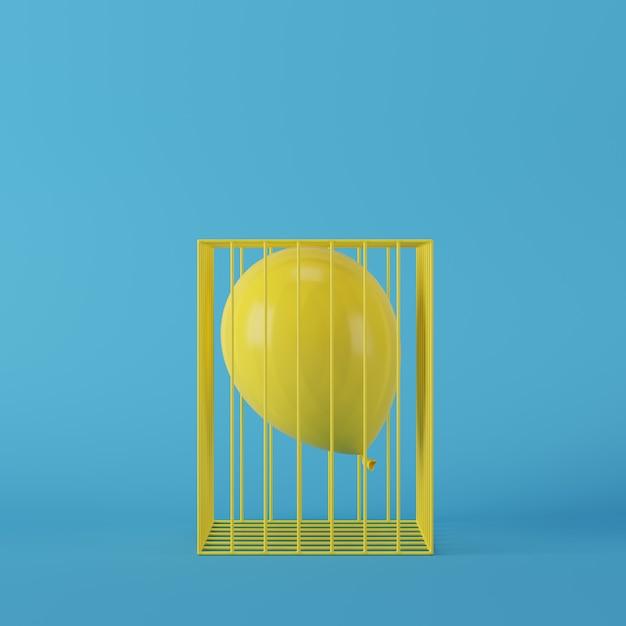 Minimaler konzeptgelbballon, der in gelben käfig auf blauem hintergrund schwimmt Premium Fotos