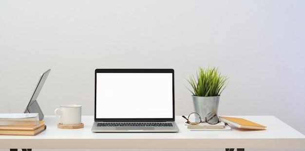 Minimales innenministerium mit offener laptop-computer und bürozubehör des leeren bildschirms Premium Fotos