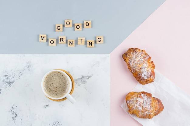 Minimales konzept des frühstücks des gutenmorgens. tasse kaffee, croissant und text guten morgen, flach zu legen Premium Fotos