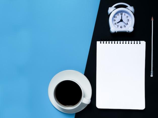 Minimales schwarzes arbeitsplatzkonzept: notizblock, bleistift, wecker, kaffee, draufsicht. Premium Fotos