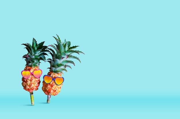 Minimales sommerkonzeptdesign der tragenden sonnenbrille der ananas auf blauem hintergrund Premium Fotos