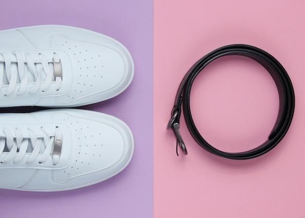 Minimalismus mode. weiße turnschuhe, ledergürtel. draufsicht Premium Fotos
