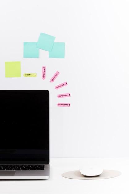Minimalistic ordnete arbeitsplatzschreibtisch mit laptop und anmerkungen über wand an Kostenlose Fotos