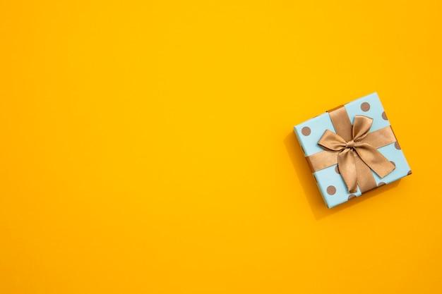 Minimalistic wickelte geschenk auf gelbem hintergrund ein Kostenlose Fotos