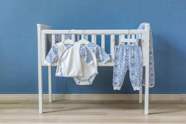 Minimalistische babyausstattung mit einem eleganten kleinen stuhl, einer dekorierten leiter und einem kinderbett Premium Fotos