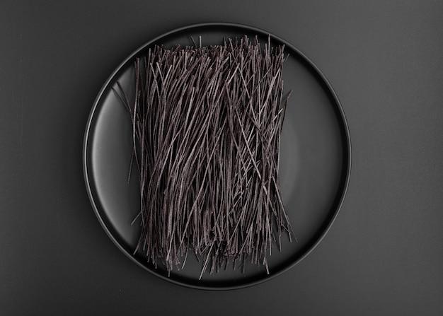 Minimalistische platte der draufsicht mit schwarzen spaghettis Kostenlose Fotos