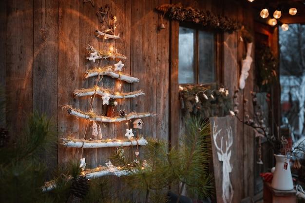 Minimalistischer moderner modischer weihnachtsbaum auf einem rustikalen hölzernen hintergrund. weihnachtsdekoration mit eigenen händen im rustikalen skandinavischen stil. Premium Fotos