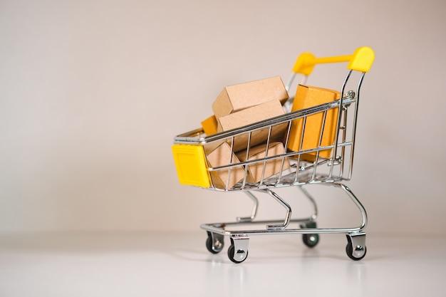 Miniwarenkorb enthalten papierkasten unter verwendung als e-commerce-, on-line-einkaufs- und geschäftsmarketing-konzept Premium Fotos