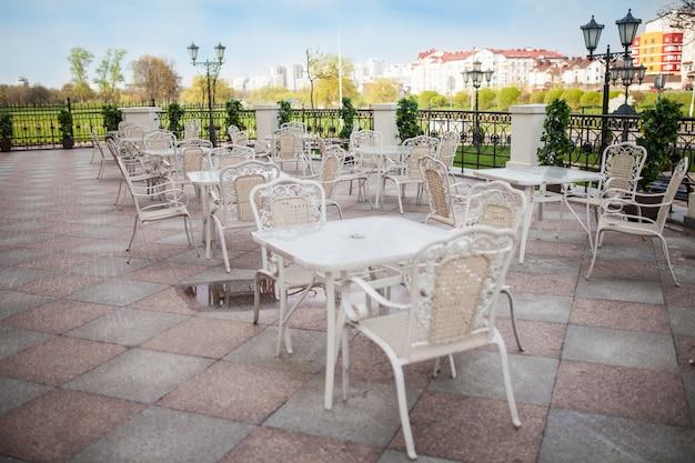 Minsk, weissrussland-23. april 2018: terrassenrestaurant mit tischen und stühlen Premium Fotos