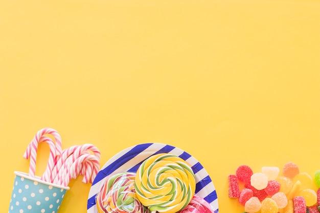Minzenzuckersüßigkeiten, lutscher und zuckergeleesüßigkeiten auf gelbem hintergrund Kostenlose Fotos