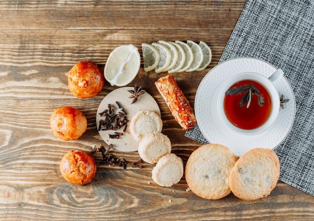 Minztee in einer tasse mit geschnittener zitrone, keksen, nelken draufsicht auf holztisch Kostenlose Fotos