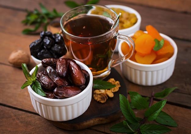 Mischen sie getrocknete früchte (dattelpalmenfrüchte, pflaumen, getrocknete aprikosen, rosinen) und nüsse sowie traditionellen arabischen tee. ramadan (ramazan) essen. Premium Fotos