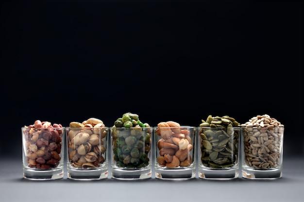 Mischen sie nüsse und samen im glas auf schwarzem hintergrund Premium Fotos