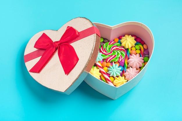 Mischen sie schokoladenbonbons liegen in der geschenkboxform des herzens auf buntem hintergrund Premium Fotos