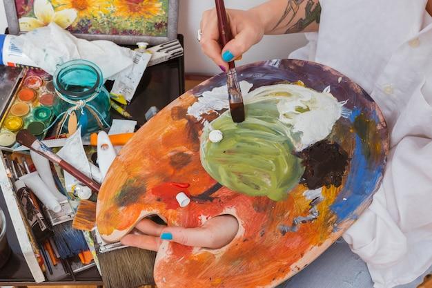 Mischende farben des malers auf palette Kostenlose Fotos