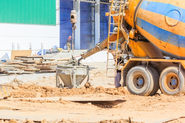 Mischer-lkw, der flüssigen beton in den turmkran-eimer gießt Premium Fotos