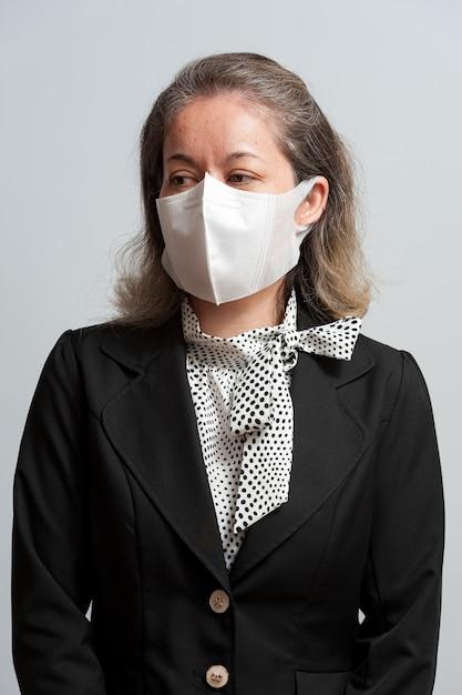 Mischlingsfrau mittleren alters in formeller kleidung, die weiße chirurgische maske trägt Premium Fotos