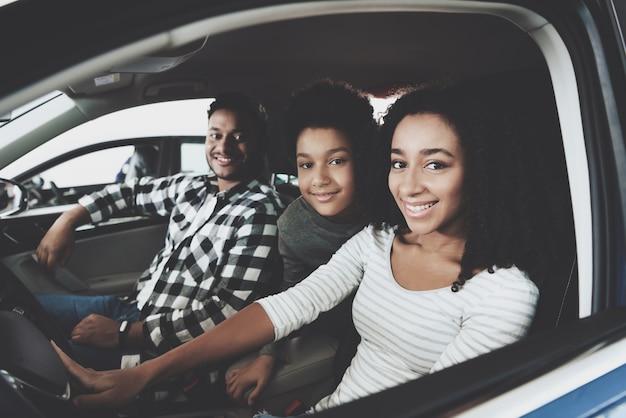 Mischrasse-verbindung und kinderfamilie, die auto kauft. Premium Fotos