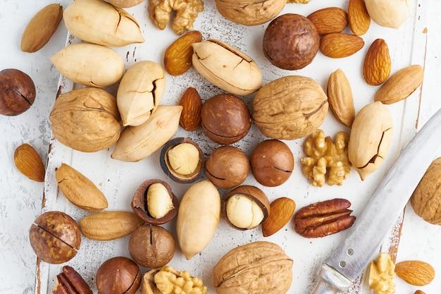 Mischung aus nüssen - walnuss, mandeln, pekannüssen, macadamia und messer zum öffnen der schale Premium Fotos
