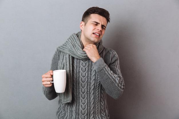 Missfallener krankheitsmann, der den warmen schal hält heißen tee trägt. Kostenlose Fotos