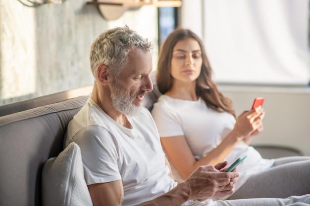 Misstrauen. erwachsener bärtiger ehemann, der auf smartphone starrt und misstrauische frau guckt, die nebeneinander auf bett sitzt Premium Fotos