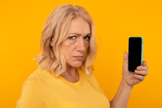 Misstrauen wütende frau mit telefon, das es isoliert im gelben studio benutzt. Premium Fotos