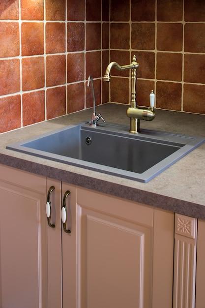 Mit einem bronzekran auf die küchenoberfläche sinken Premium Fotos